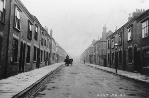 A black and white photograph of Clarendon Park in the early 1900s. A single horse and cart is in the distance.